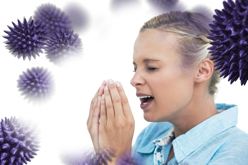 Blonde woman sneezing with hands in front of her face against virus.jpeg