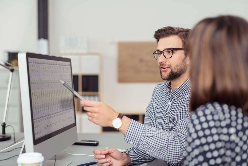 Proficient young male employee with eyeglasses and checkered shirt, explaining a business analysis displayed on the monitor of a desktop PC to his female colleague, in the interior of a modern office.jpeg