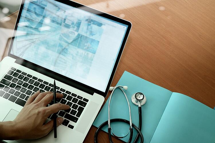 top view of Medicine doctor hand working with modern computer and smart phone on wooden desk as medical concept.jpeg