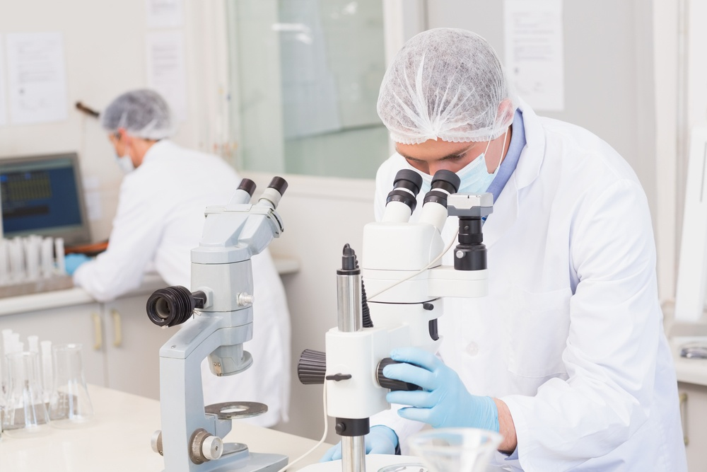 Scientists working attentively with microscopes in laboratory.jpeg